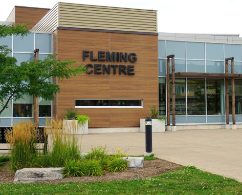 Armor stone and ornamental grass in front of the permable paving walkway towards the Fleming Centre