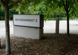 Signage for Environment 3 building at University of Waterloo in a mulched in area in front of the building surrounded by a couple trees