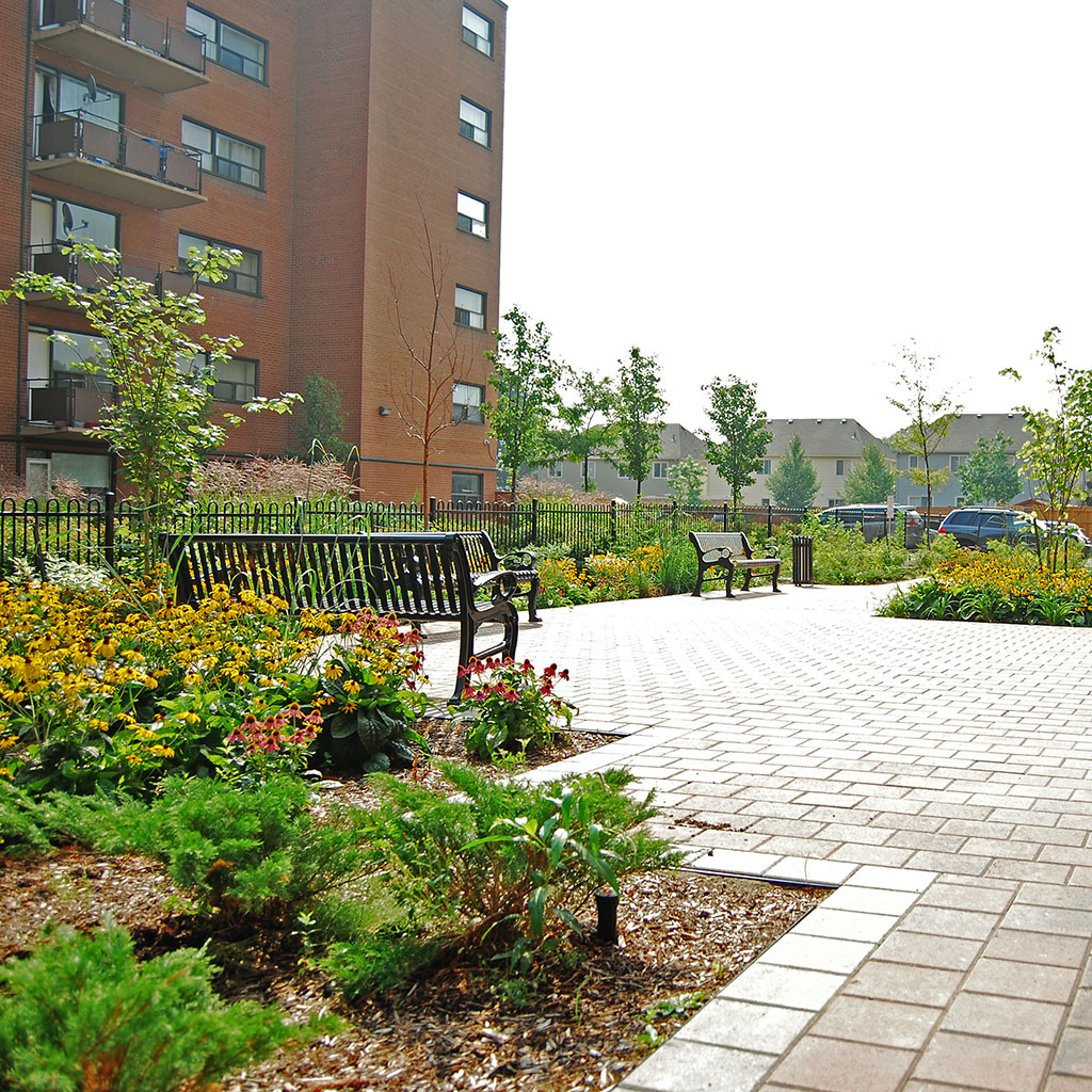 Paver stone pathway with small shrub gardens along the edges and park benches throughout