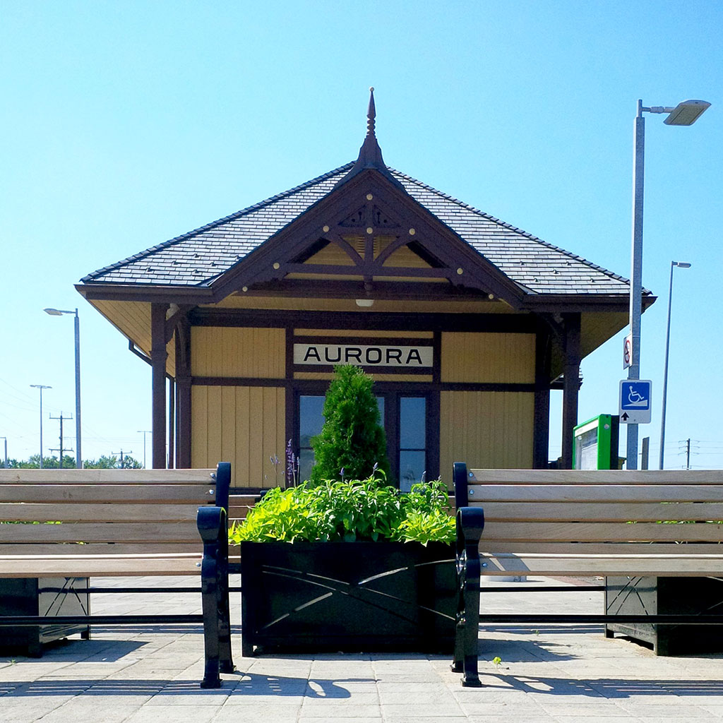 Aurora Go station outpost building behind two park benches with a small black planter box with green plants inside