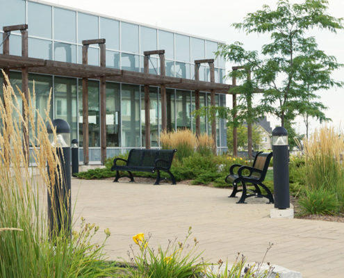 Permeable paver walkway seating area guided by two light posts surrounded by gardens of ornamental grass