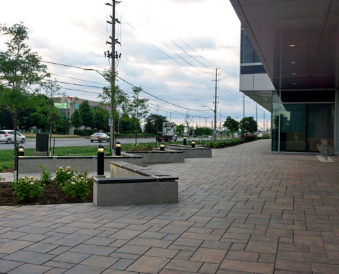 paving stoned path with benches and a garden at the entrance to an industrial building