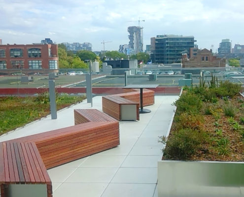 Zig-zag benches on a green roof space with large planter beds