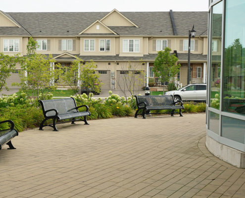 Permeable paver walkway with benches in a small seating area around the Lincoln Public Library