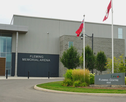 Island planter in the round about with ornamental grass and small tress and shrubs behind the Fleming Centre sign