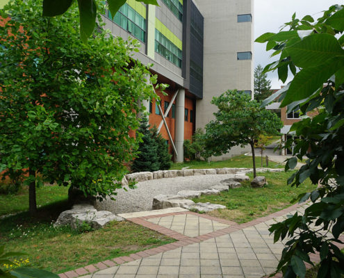 Permeable paving path leading to a gravel area of a bioswale on the side of a building