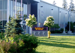 The front entrance to the Cobourg Community Centre with small trees and bushes surrounding the metal sided structure