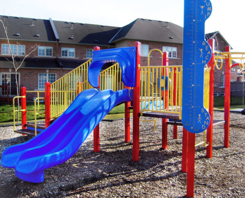 Red, blue, and yellow playground equipment with two slides and monkey bars