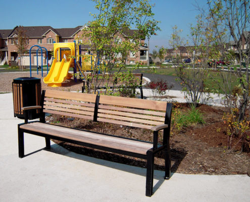 A park bench in front of a garden planter with small trees at the playground in Harvest Bramalea