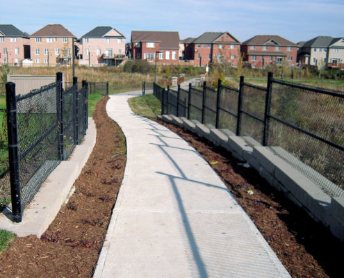 Concrete path in between mulch planters winding through a natural bioswale