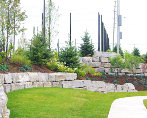 large stones retain a mulch flowerbed on a slope overlooking the grass and sidewalk below