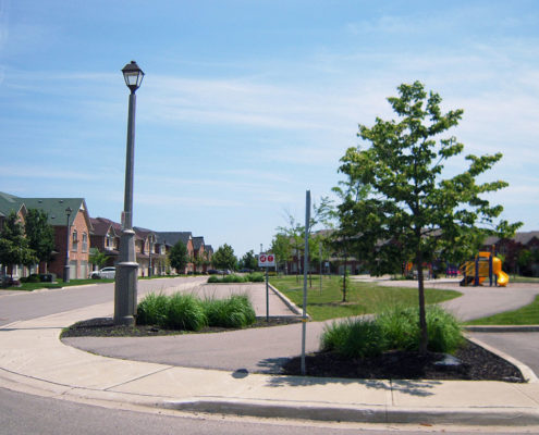 Ornamental grass and a small tree sit in planters at the entrance to the park at Harvest Bramalea