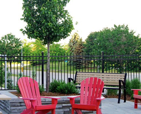 Muskoka chairs on a paver stone patio that is fenced in with trees in the background