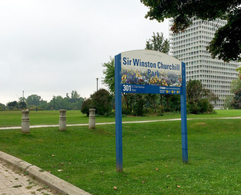 Signage at the entrance of Sir Winston Churchill park with lush grass and trees in the background