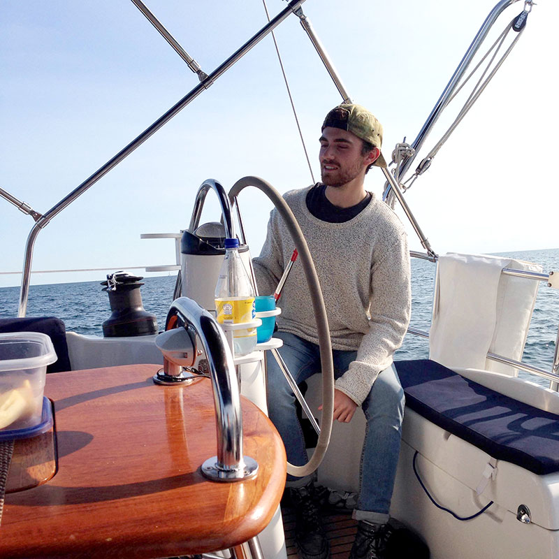 Staff member seated at the helm of a sailboat in lake Ontario