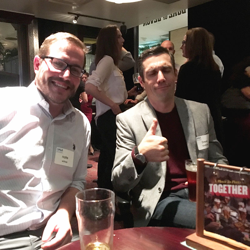 Nate and Drew enjoying a pint of beer seated at an OALA event