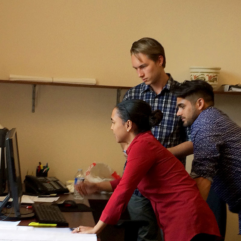 Three staff members reviewing work on the computer screen in the office