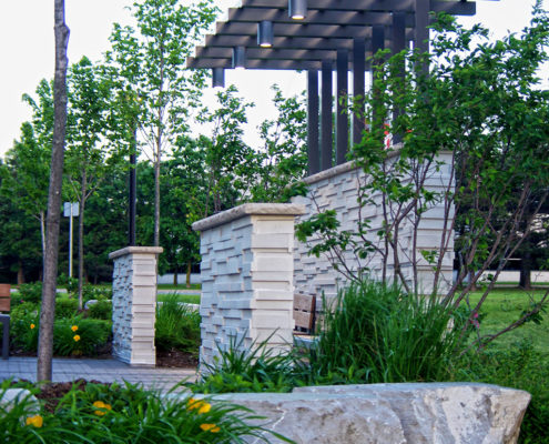 Stone wall and trellis offers shelter from the road in a quite permeable paving seating area with benches