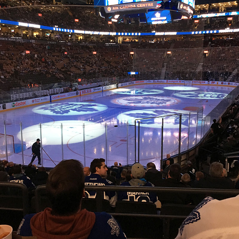 Giant leafs logos shine down on ice surface at Maple Leafs game in Toronto