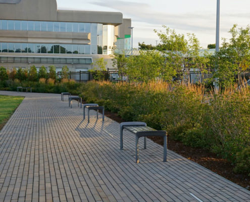 Permeable Paving walkway with benches and small shrubs leading towards the office building
