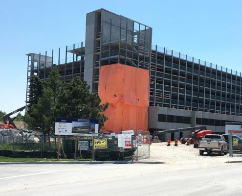 Humber College's Barrett Centre construction area with the steel structure being erected. An orange tarp covers a corner of the building