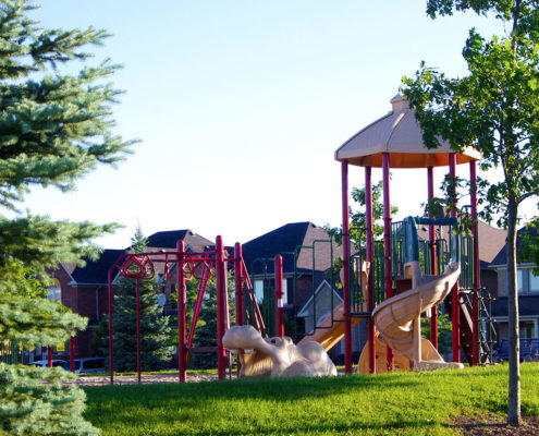 Trees sit surrounding the playground equipment that include a giant plastic hippo and a slide