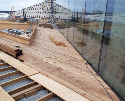 Decking being laid for the usable green roof at Humber College Barrett Centre next to the floor to ceiling glass windows
