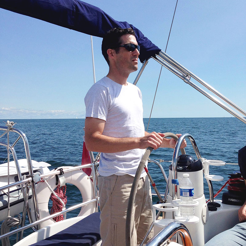 Staff member standing at the helm steering a sailboat at a staff outing