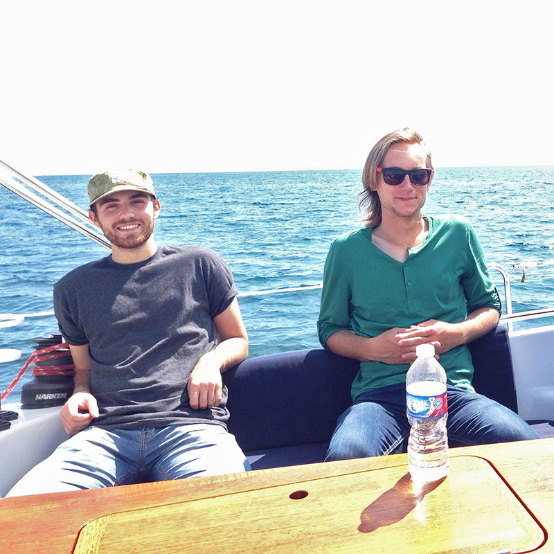 Two staff members seated on one side of a sailboat at a staff outing