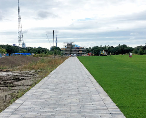 A laid stone walkway in Sir Winston Churchill park with the CN Tower off in the distance