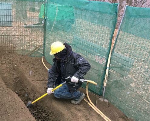 Hydro Vac professional using a hydro Vac to remove soil around existing tree roots to perform a root investigation