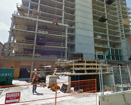 William Thomas Building under construction with exposed concrete and fencing surrounding the work site