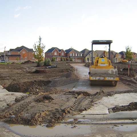 Construction roller parked on a landscape site during construction phase before planting