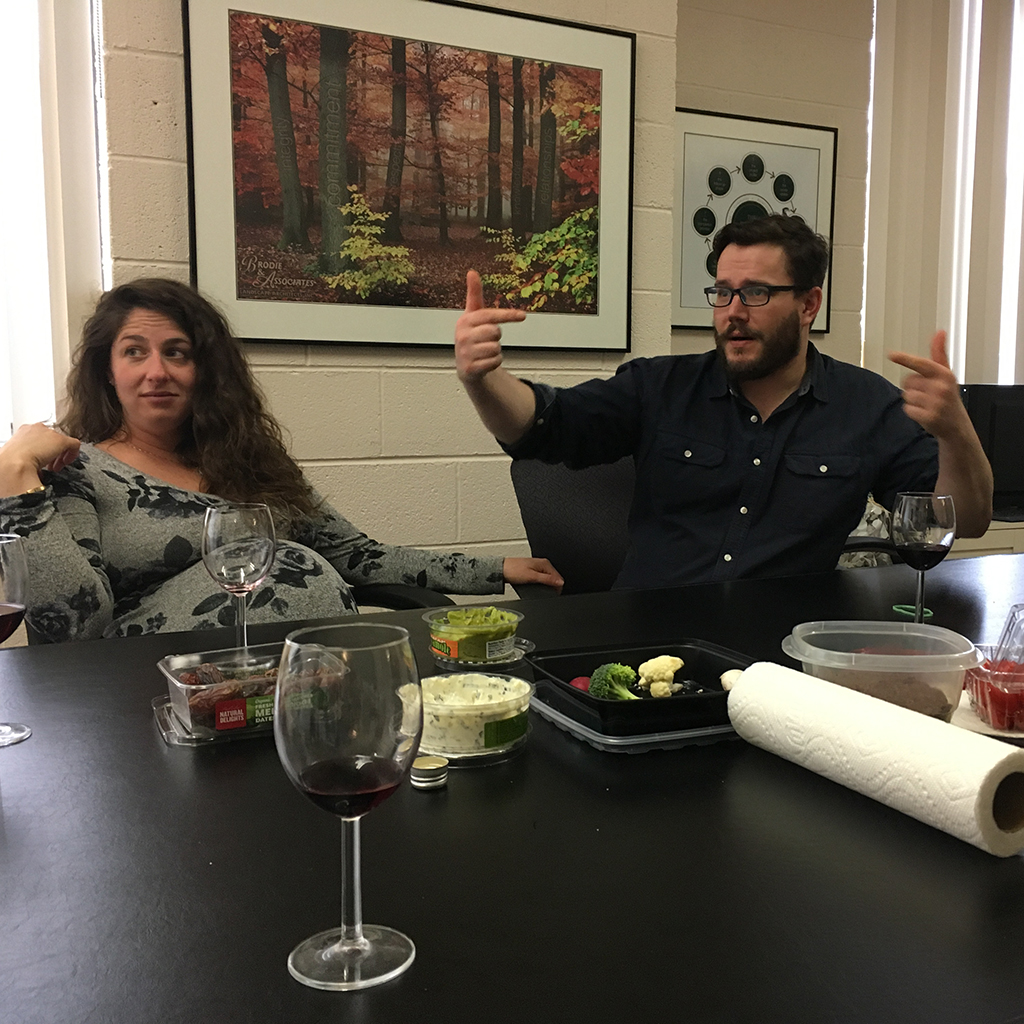 Ilana and Nate sitting around the boardroom table at the office of Brodie and associates