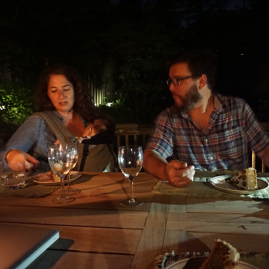 Alana, Nate and baby Mo eating dinner in Helle's backyard at our staff BBQ